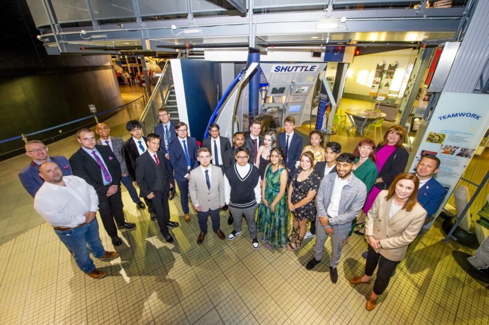 Students stood in a semi-circle next to a rocket at the National Space Centre